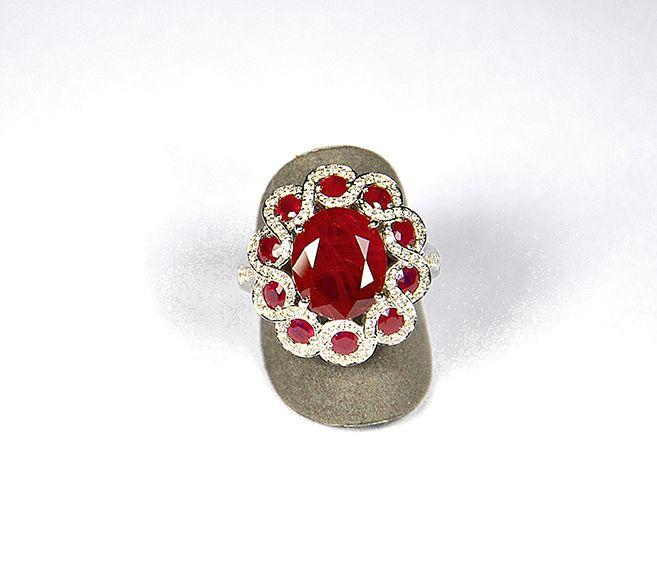 Bague en or gris (750 M) ornnée d'un rubis central ovale facetté pesant 4,70 cts entouré de 10 rubis ronds facettés plus petits bordés de diamants en pavage.  Accompagnée d'un certificat SVD attestant :  -du poids de la pierre  -de son origine Birmanie  -de sa qualité naturelle avec traitement thermique  Brut : 9,35 g  Estimation : 7.000/8.000€ puis 5.400/5.600€