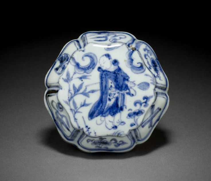 Lobed round box and cover decorated in underglaze blue. This six-lobed box has a deep base which tapers towards a narrow unglazed base; its cover has sloping sides and a flat top. It is painted in underglaze blue cobalt with a design of a figure dressed i