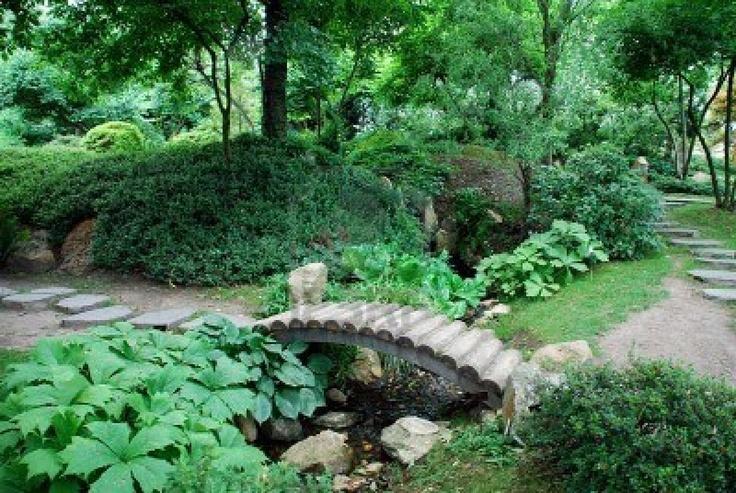 Japanse tuinen met veel bloemen soorten en een houten boog brug Stockfoto