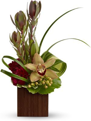 bouquet includes bronze cymbidium orchids, burgundy carnations, peach hypericum and leucadendron accented with assorted greenery.