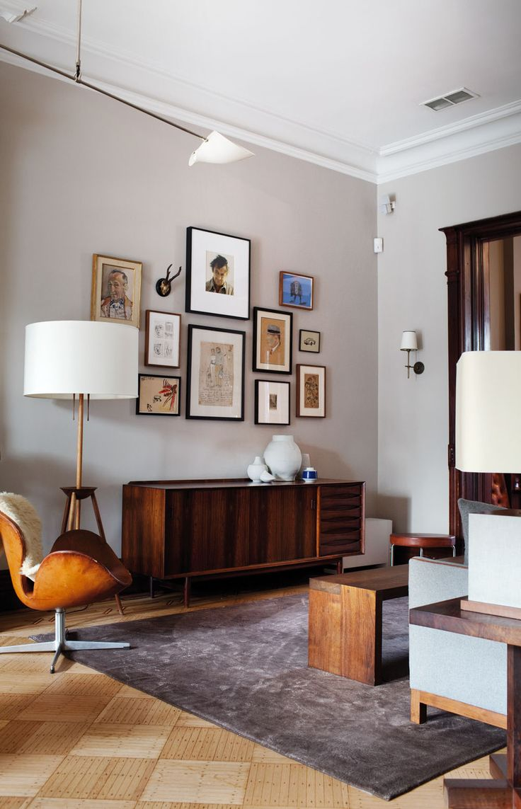 Home in Brooklyn. An old, tan Swan chair with clean line 50s furniture and a collage of paintings on the wall. Love it