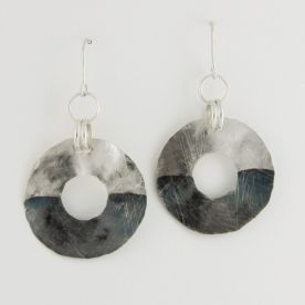 Silver circles made of thin hammered sheet metal. The surface is hammered, scratched and partially oxidised. The total length of the earrings – 5,7cm. The circle diameter – 33mm.