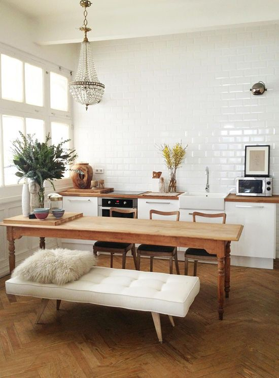 kitchen // glass chandelier // white tufted bench // fur pillow // wood and subway tile