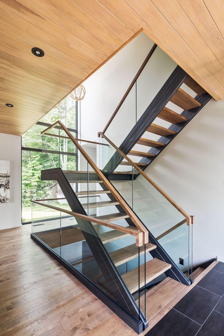 Madeira e pedra cobrem o exterior desta casa moderna de vários níveis na floresta   – Treppe