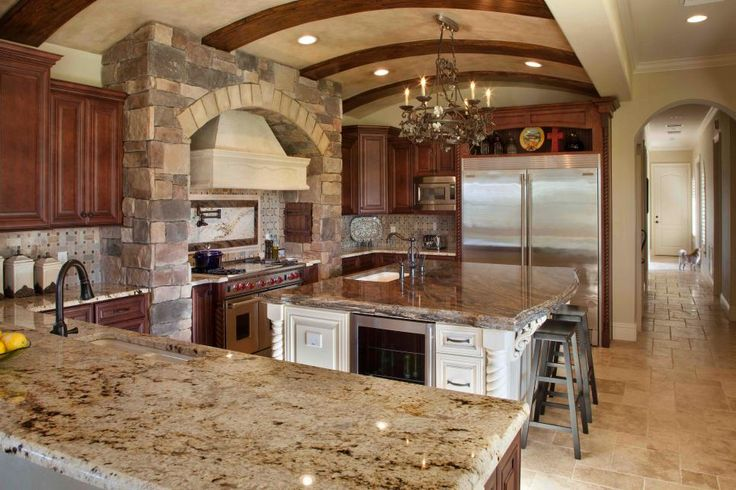 A brick barrel ceiling with rough-hewn beams sets the tone in this Mediterranean-style kitchen. The hefty range hood is framed by a muted stone hearth and tumbled tile backsplash, while a large island offers storage and functionality in the eat-in kitchen.