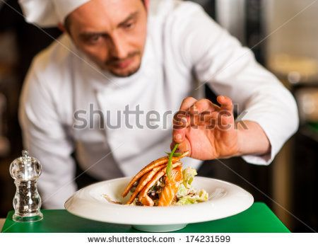 Chef adding final touch to delicious baked salmon