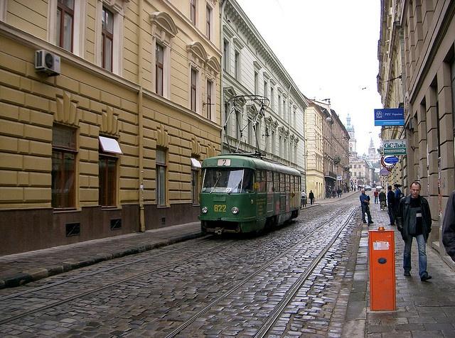 A green tram rolls along the wet streets of Lviv