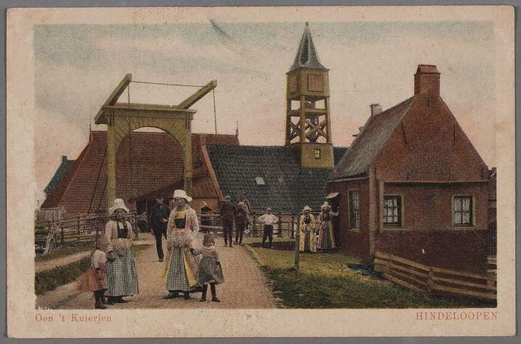 Oen 't Kuierjen HINDELOOPEN klederdracht op dijk bij Sluisbrug Dijkweg met grote ophaalbrug. Op de voorgrond en rechts bij het huisje voor de brug enkele vrouwen en kinderen in klederdracht. Op de achtergrond het sluishuis met klokkentoren en leugenbank. Aan het huisje op de voorgrond zit een houten regenpijp en schoorsteenafdekking. 1900-1936 #Friesland #Hindeloopen