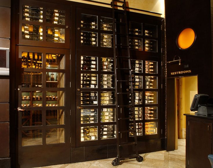 Spacious Cabinets Using Attractive Wine Cellar Design With High Dark Ladder On Stone Flooring