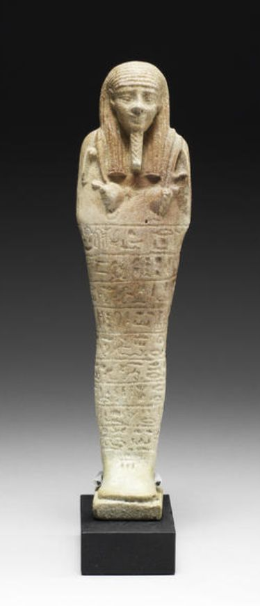 An Egyptian green glazed composition shabti for #Tjaiinherimu  Late Period, circa 664-525 B.C. Of typical mummiform, holding agricultural implements with seed-bag slung over the left shoulder, the front impressed with nine horizontal bands of text for 'The hereditary noble, royal scribe of amounts of all offerings, prophet, Tjaiinherimu, born to Merptah', 7¾in (19.5cm) high, mounted