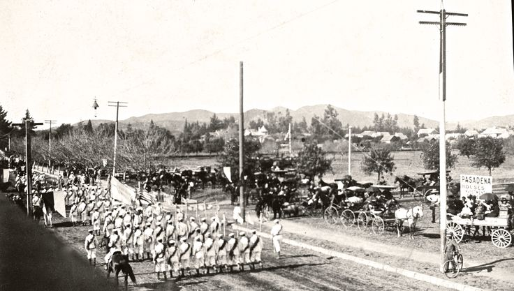 "Note the sunny skies. Note the empty land. Note, if you will, the ""Pasadena Real Estate"" sign in the lower right corner of this 1898 Rose Parade picture.  The Tournament of Roses Parade was originally a come-on, in a way–a sales pitch to those out east suffering the winter cold. ""Here in Pasadena,"" the parade seems to say, ""we're warm on New Year's Day! We even have roses growing in such profusion we cover our wagons with them!"""