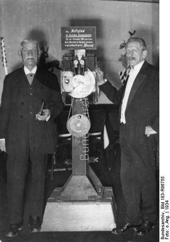 """Max Skladanowsky (rechts) mit seinem ersten Filmprojektor """"Bioskop"""". Links sein Bruder Eugen, der sein erster Darsteller in den von ihm gedrehten Kurzfilmen war.  Dating:1934"""