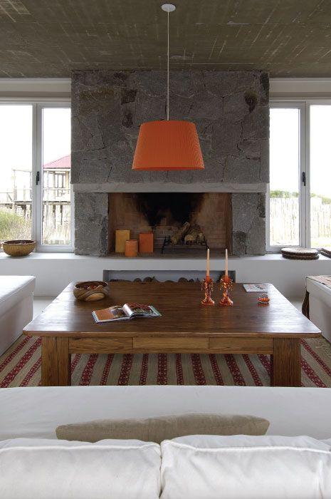 <span>Mesa ratona de madera, lámpara de arpillera naranja y chimenea de piedra con troncos y velas naranja.</span></p>