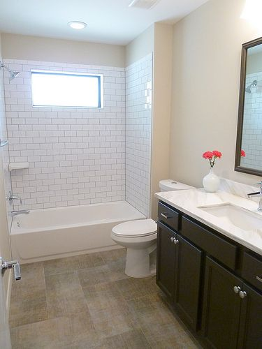shower with window, ledges, subway tile, no glass. Framed mirror.