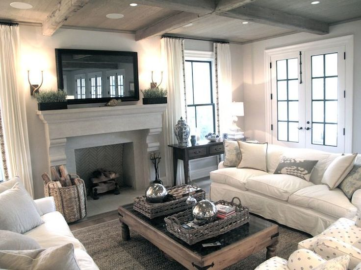 Jane Green    Figless Manor - Chic, cozy living room with framed TV over stone fireplace, herringbone firebox, rustic wood coffered ceiling, French doors, sisal rug, white curtains with ribbon trim, white slipcover sofas, gray pillows and wood cocktail ta