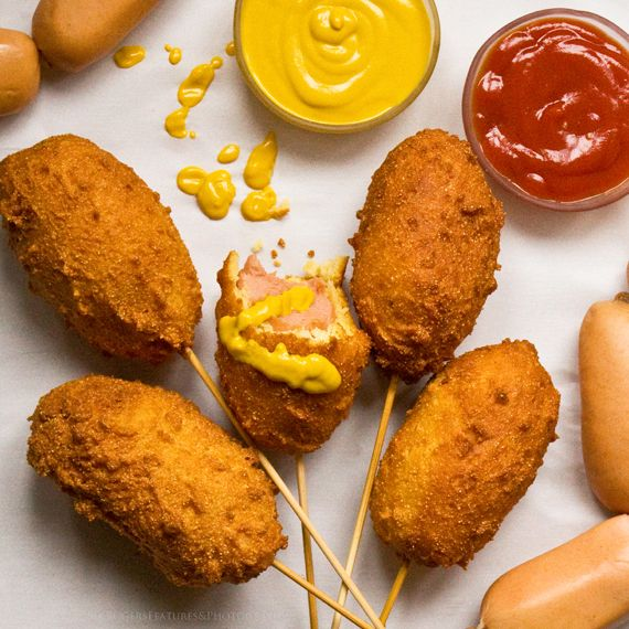 Corn dogs! Sausages dunked in thick, cornmeal batter, fried and served hot and crispy, with mustard.