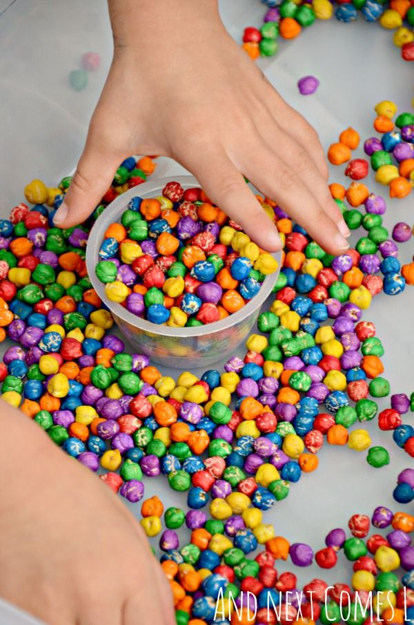 Playing with rainbow dyed dried chickpeas - a great sensory bin filler for toddlers and preschoolers from And Next Comes L