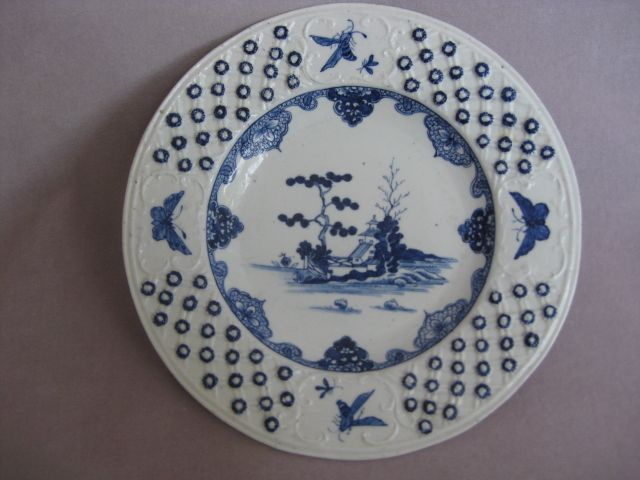 """A fine Derby blue and white plate with a basketwork border with applied florets. Four panels to the edge containing insects and with a Chinese building in landscape to the centre. Unmarked  Circa  1758 W 8 1/4"""""""