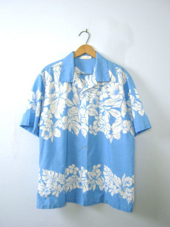 One vintage 1980s blue hawaiian shirt, tropical shirt, Aikane shirt, size large  - Pointed collar. - 4 button closures going down the center front. - 1 slide chest pocket. - Color scheme: sky blue, white and grey.  | CONDITION | A+. Gently used vintage item.  | BRAND | Aikane. Made in USA.  | SIZE | Not marked. Fit is about a mens Large (USA). *** PLEASE compare the measurements below to a similar item that fits you for the best sizing! ***  ~ Garment laying flat. Double measurements where…