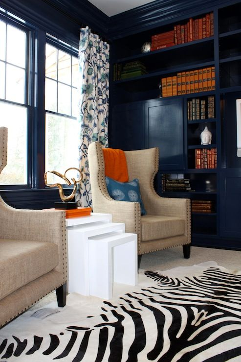 dark navy, high gloss paint....with linens, pop of orange, the white area rug and zebra plus the white tables make the room or else it would feel too dark