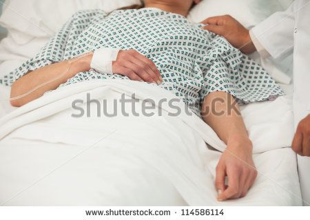 Old sick lady lying in hospital bed - stock photo