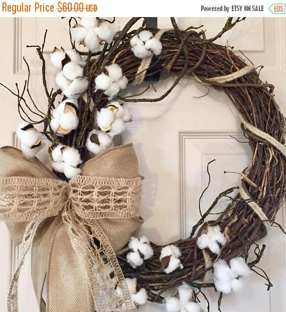 You have found a perfectly simple rustic cotton wreath for your country home! Created with a 16 grapevine. I then wrapped a braided jute cord around the entire wreath. Secured to the side of the grapevine are green/brown branches and sprays of cotton. Sitting within the cotton and branches is a large bow. The ribbons used in the bow include a natural burlap and a natural jute netting. This wreath measures approximately 24 high, 19 wide and 6 deep. Because my wreaths are handcrafted, no...