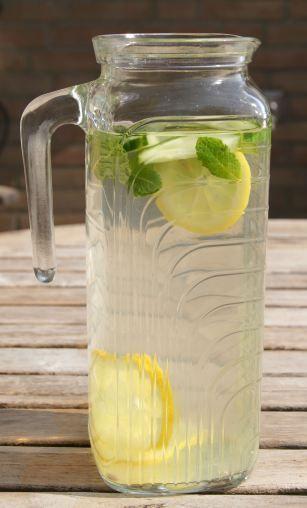 Detox water met citroensap en munt. Ook lekker en gezond: appel in dunne schijfjes en een kaneelstokje