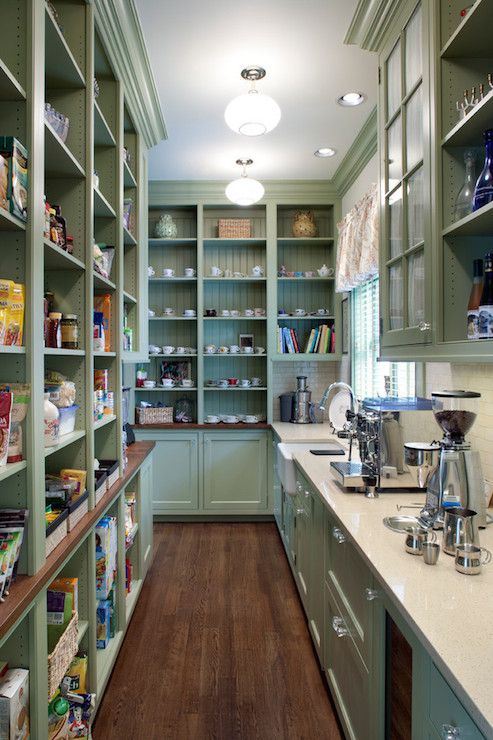 Stunning galley style butler's pantry with green shaker cabinets painted Benjamin Moore Georgian Green accented with crystal pulls and ivory quartz countertops with an ivory subway tiled backsplash. The butler's pantry features floor to ceiling shelving with beadboard backed shelves along the back wall to the left of an apron sink with gooseneck faucet situated below the window illuminated by a semi-flushmount schoolhouse pendant.