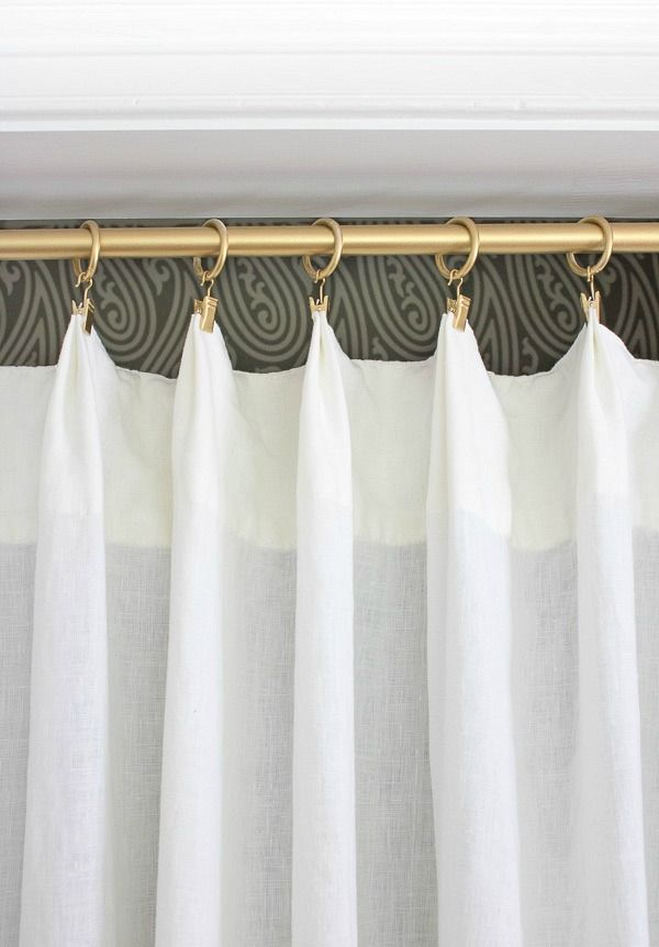 Rod and curtain rings spray painted gold as part of a closet makeover ditching those ugly bifold doors!