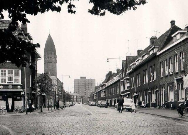 tot: 1965-12-31 Beschrijving: De Lekstraat gezien vanaf de kruising met de Hoofdstraat in de richting van de Nieuwe Maasstraat. Links de Heilig Hartkerk en op de achtergrond een hoogbouwflat aan de Havendijk.