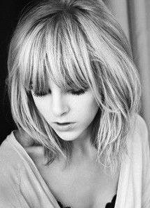 Very feminine haircut with long chunky bangs.