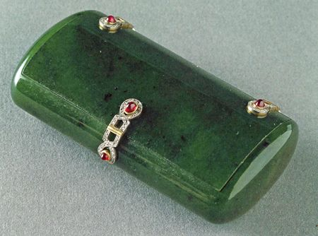 Fabergé Jade Cigarette Case – A 8.3cm long box with white enamel decoration, chiseled laurel leaves and 8 ruby cabochons. Made by Henrik Wigström, the other jade specialist of Fabergé