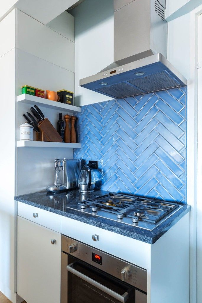Blue tile laid in a herringbone pattern creates a striking backsplash in this Upper West Side kitchen renovation.