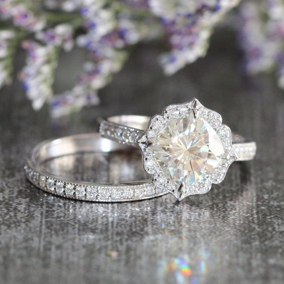 This bridal wedding ring set showcases a floral engagement ring with a 8x8mm cushion cut forever brilliant moissanite set in a solid 14k white gold