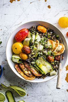 A fresh lentil salad topped with fried halloumi, roasted tomatoes and zucchini