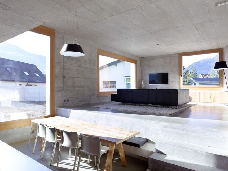 Maison Fabrizzi by Savioz Fabrizzi Architectes /   瑞士 Conthey 擁有大窗景的混凝土私宅,最大限度地開窗引入週邊山景,使室内空間明亮舒適,搭配橡木帶來溫暖的居家感受。 客餐廳採開放式設計,餐廳的水平面稍低於客廳,除功能作出區隔外,用餐空間的視感更顯挑高。