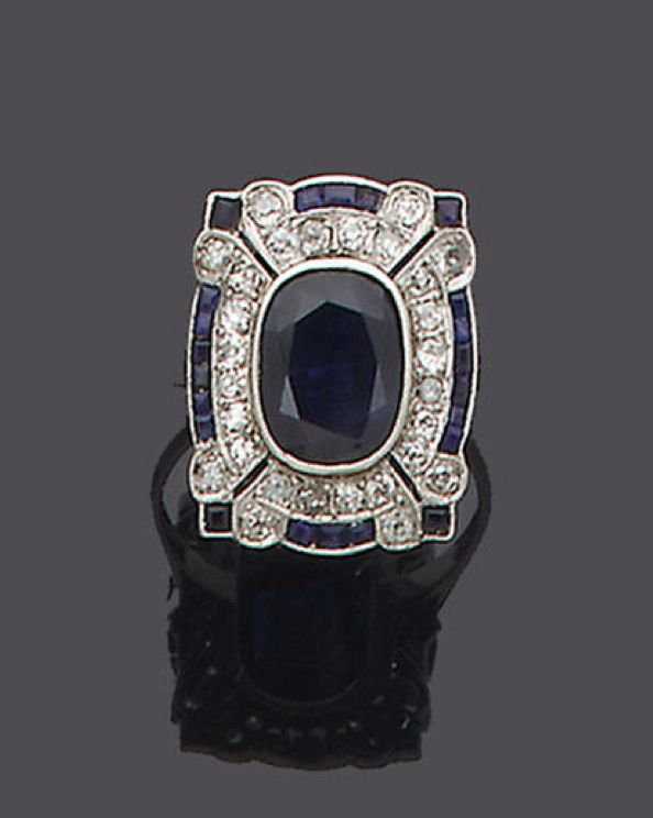 An art deco sapphire and diamond panel ring, circa 1920 The rectangular-shaped plaque millegrain-set to the centre with an oval mixed-cut sapphire, within a single-cut diamond border and a further calibré-cut sapphire and single-cut diamond surround, diamonds approx. 0.30ct