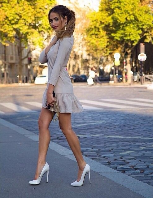 Toned legs in a short gray dress and white high heels street style.