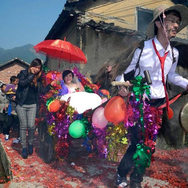 Newlywed groom Meng Jun (R), 29, pulls a cart carrying his bride Zeng Shuangying, 25, during a traditional wedding ceremony in Shitang village of Gongcheng Yao Autonomous County, Guangxi Zhuang Autonomous Region. Many locals still follow the tradition of carrying out pranks to make fun of newlywed couples, including preparing costumes for the groom, painting his face with ink, setting barricades for the cart he has to pull, and so on.