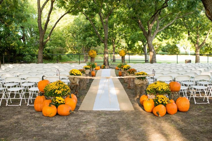 This beautiful outdoor fall wedding was held at a rustic Texas wedding venue called 1899 Farmhouse. The charming country setting for the ceremony featured large pumpkins, yellow mums and a burlap runner. Keeping with the fall color theme, the bouquets were filled with red and orange flowers, with touches of white. The color of the ….