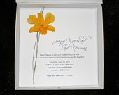 Fabulous couture boxed wedding invitations. This is a simple, striking design, embellished with a real orchid flower blossom and accented with a few blades of grass. This gorgeous flower is preserved to maintain its shape and color for years. Invitation, reply card and matching envelope are tucked into our lovely white paper box with snap closure.