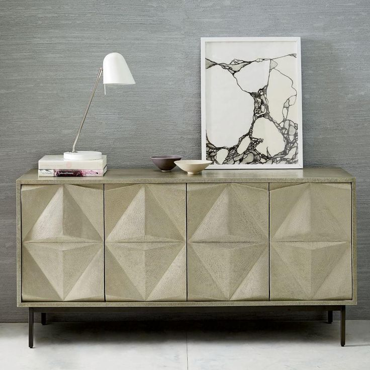 We took the architectural design of our Geo Console and gave it a polished makeover. Made of metal-wrapped mango wood, our Brass Clad Sculpted Geo Sideboard is a strikingly modern storage solution for dining rooms or entryways.