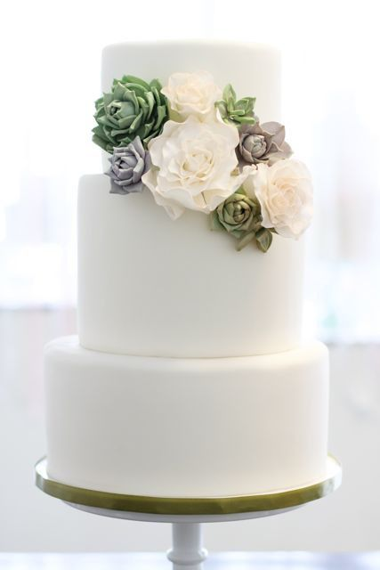 The wedding cake will feature a cluster of pale green succulents, ivory roses, white ranunculus with hints of dusty miller, bay laurel, and silver dollar eucalyptus close to the top balanced by another cluster on the other side, lower of the same florals.