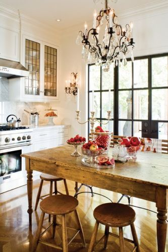 Stained glass windows on the cabinetry and a rustic table bring warmth to this white but beautiful kitchen.