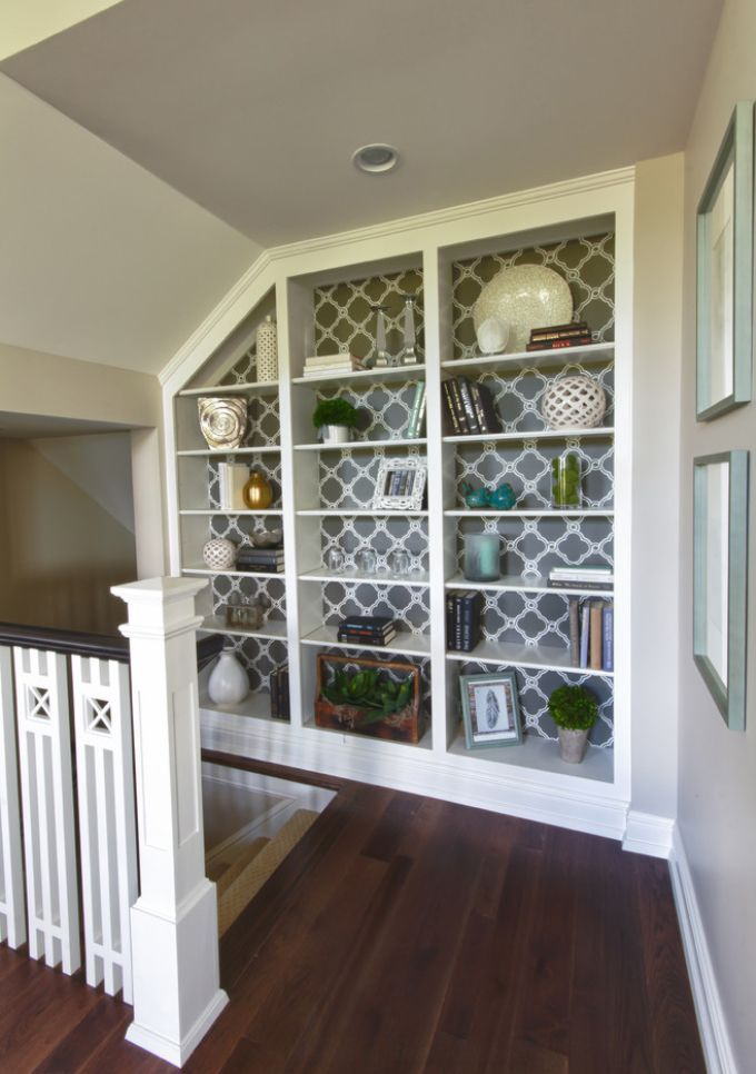 Built-in bookcase in nook at top of stairs. Love the wallpaper background. Adds to the decor.