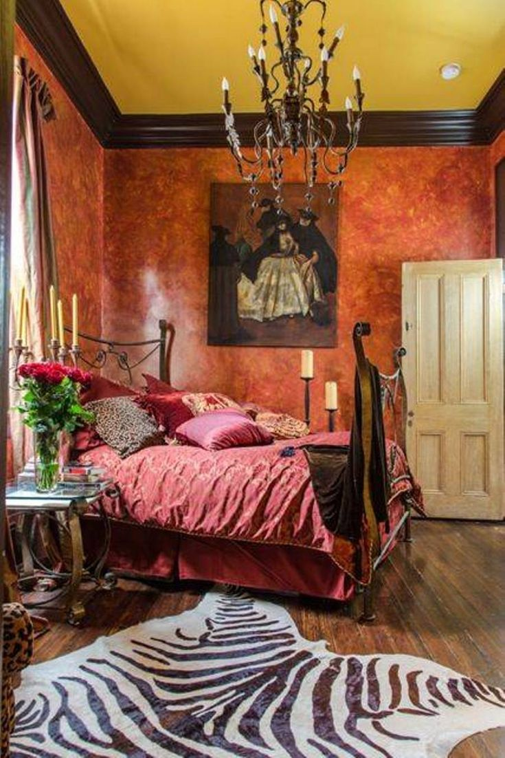 Bohemian Style Master Bedroom With Color Washed And Chandelier And Red Bedding And Side Table And Candelabra And Zebra Print Rug