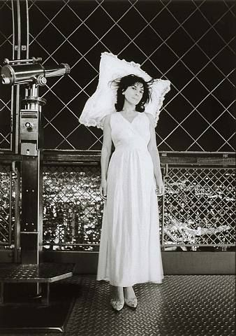 (A) Sophie Calle lors d'une performance où elle recevait des visiteurs dans son lit en haut de la Tour Eiffel #UneSource