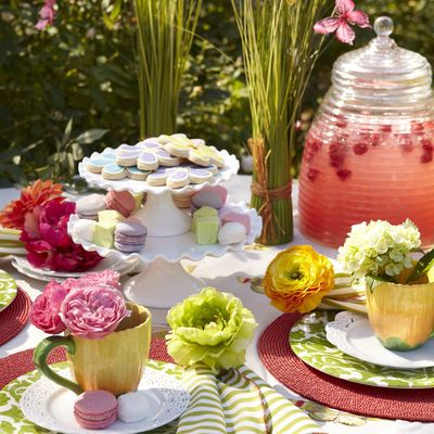 Spring party. White Scalloped Cake Plates. coral placemats, green striped napkins, flower napkin rings, flower rmugs, green melamine plates, spring grass bushes