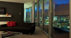 One of our beautiful two-bed serviced penthouses in Birmingham by night. The floor-to-ceiling windows open on to a wraparound balcony overlooking the city.