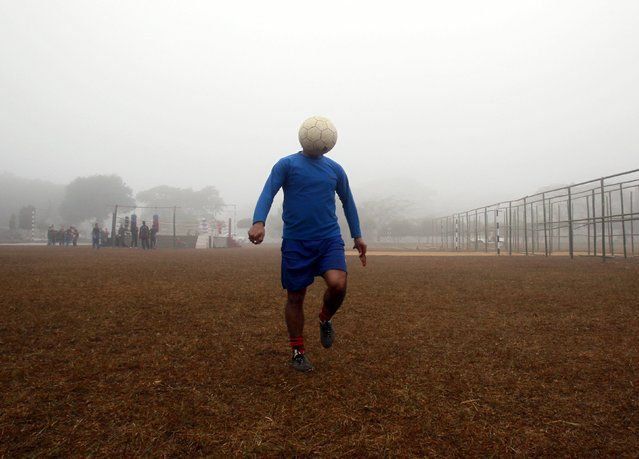 A man controls a ball during his soccer practice in a public park on a foggy morning in Agartala, capital of India's northeastern state of Tripura, in this January 12, 2015 file photo. (Photo by Jayanta Dey/Reuters) | www.ghantagiri.com #ghantagiri